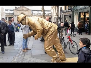 Golden man London street performer, floating and levitating trick Covent Gardens